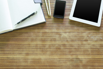 Office table with tablet, pen on notebook, smartphone on old wooden table.