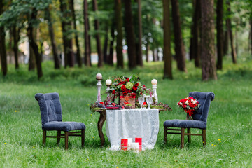 Wedding table decor: chairs and candles, flowers, ceramic dishes with fruits, standing on the lace tablecloth and moss. Bridal details and decorations, romantic dinner at the forest