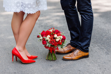 Wedding details: stylish red and brown shoes of bride and groom. Bouquet of roses standing on the ground between them. Newlyweds standing in front of each other
