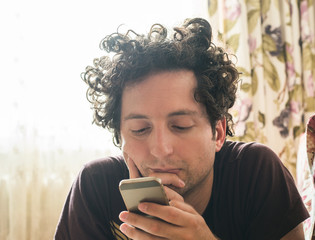 Portrait of a relaxed Caucasian man using smart phone at home