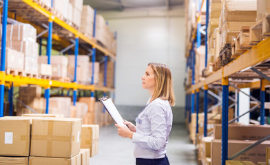 Woman warehouse worker or supervisor with clipboard.