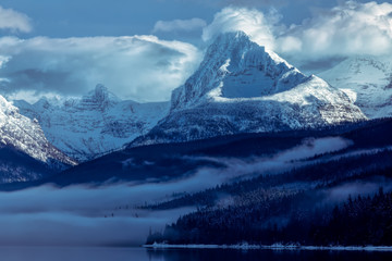 Majestic mountains above Lake McDonald in Glacier National Park, Montana in winter with clouds and fog