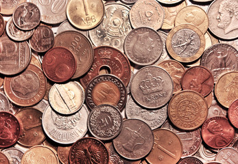 Background from coins. The currencies of different countries as a symbol of abundance of money. Backdrop of the scattering metal cash. Horizontal location.