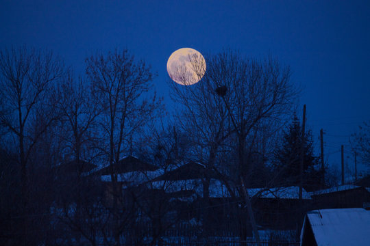 the full moon rising over a country house in winter