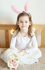 one cute little girl in rabbit ears is sitting on the sofa with Easter baskets