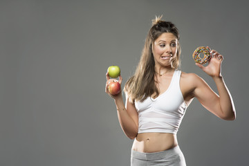 Beautiful white fitness model wearing a grey and white fitness outfit  holding two apples in her right hand while looking at a junk food donut in her right hand with a deciding look on her face