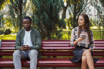 Woman sitting in park with man using smartphone