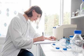 Woman writing in laboratory