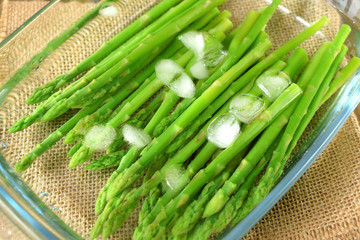 Green asparagus in cold water in a glass dish