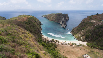 Beach with with azure water, rocky mountains and clear water at sunny day. Clear blue ocean waves rolling to the beach. Nusa Penida, Bali, Indonesia. Travel concept.