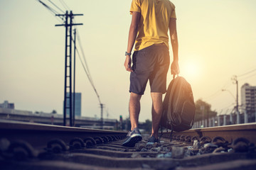 Man walking on the railroad and handle bag