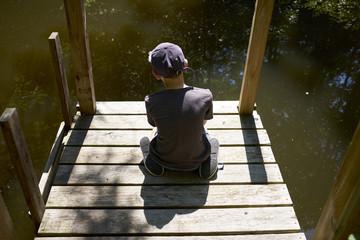 Boy sitting alone on dock