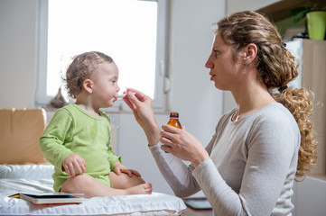 Mother giving sick child a syrup