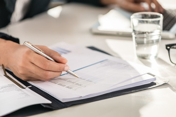 Close-up of the hands of a business woman sitting at desk while checking numbers printed on paper