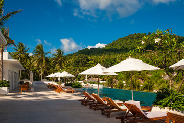 A perfect holiday photo of empty deck chairs and patio umbrellas in between, lined up in front of an infinity pool on a tropical island with a beautiful hill in the background.
