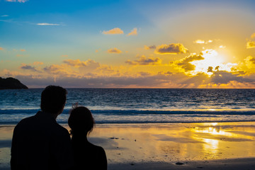 The rear view silhouette of a couple holding each other during sunset on the beach.