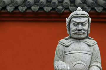 Statue of soldier in stone inside buddhist temple