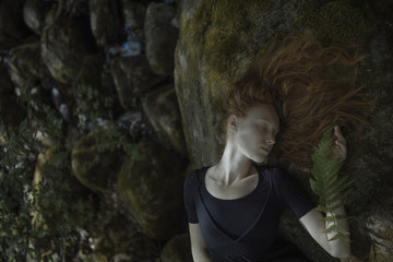 Caucasian woman with red hair laying on rock