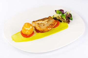 fried fish sauce tomatoes appetizer greens on a plate