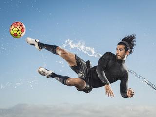 Water spraying on man kicking soccer ball