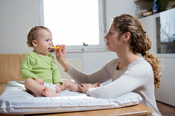 Mother teaching baby how to brush teeth with toothbrush