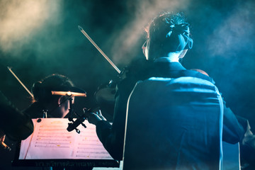 Concert / View of musician playing the violin in concert at night. Movement, Soft focus.