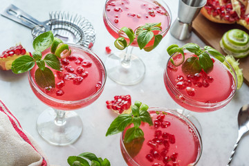 Pink Pomegranate Basil Martinis or Gin Smash Cocktails on Marble Bar Top with Ingredients and Tools