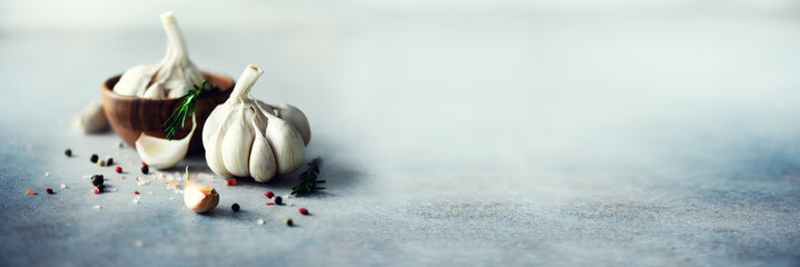 Garlic, rosemary, black pepper, salt on grey concrete background. Top view, copy space. Banner
