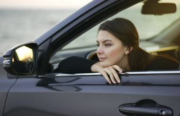 Thoughtful woman leaning on the car window