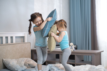 Two kids girls playing with pillows at home