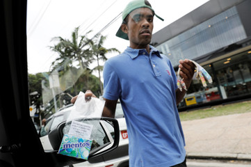 A man sells sweets by a traffic light in Sao Paulo