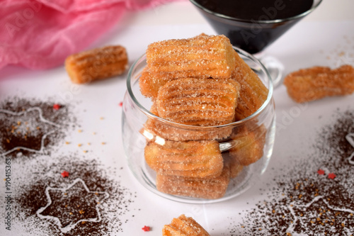 Spanish cookies Churros in a glass jar and chocolate sauce