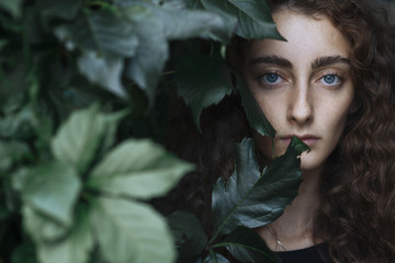 Portrait of serious woman behind leaves