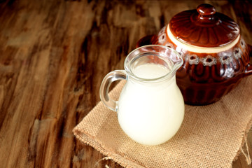 Milk whey in a glass jug and a clay pot in the background