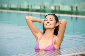 Asian woman resting at pool. Woman with relax emotion.