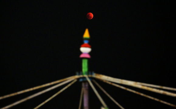 """A lunar eclipse of a full """"Blue Moon"""" is seen rising over a roller coaster ride in Chennai"""