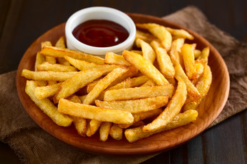 Fresh homemade crispy French fries with a small bowl of ketchup on wooden plate, photographed with natural light (Selective Focus, Focus one third into the fries)