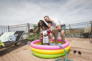 Parents posing for selfie with children in inflatable swimming pool