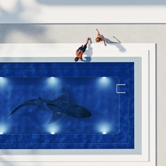 Couple watching shark in swimming pool