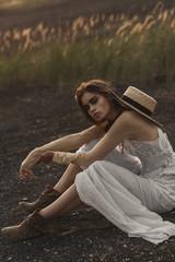 Sexy Caucasian woman wearing white dress sitting in field