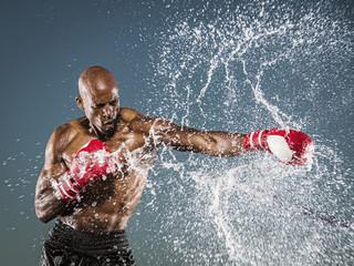 Water splashing on black boxer punching