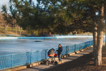 Young woman in blue coat walking in winter park near frozen lake with little child baby in orange baby carriage, on nature, green trees. Mother and kid. Parenthood, love, parents, children concept.