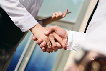 woman and man shake hands on the background of an office building.