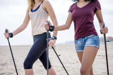 nordic walking two girls walking on beach with sticks Wall mural