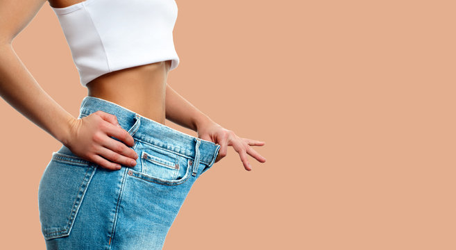 Weight loss. Woman in oversize jeans on pastel background