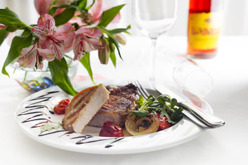 Succulent thick juicy portions of grilled fillet steak served with tomatoes and roast vegetables