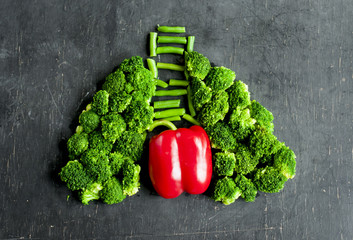 fresh broccoli, red pepper, asparagus in the form of human lungs lined on a dark background. Useful vegetables to maintain lung and heart health.