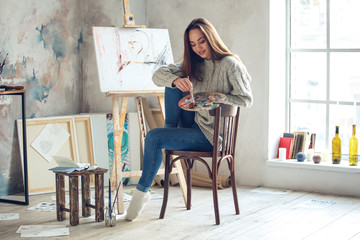 Young woman artist painting at home creative looking down smiling