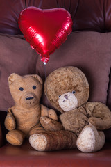 Valentines day. Old aged vintage teddy bear couple. Teddies sitting holding hands with red heart balloon. Retired but clearly still in love.