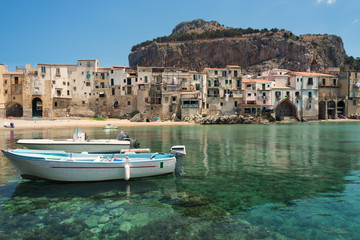Cefalu old town and port with city beach and clear sea in Sicily